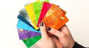 mano di donna che tiene un ventaglio di carte prepagate colorate